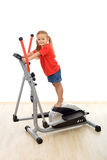 Little girl standing on top of elliptical trainer Stock Photography