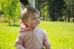Little girl standing by a tree Stock Photo