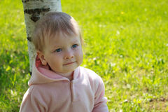 Little girl standing by a tree Stock Image
