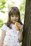 Little girl standing by the tree and eating a croissant Royalty Free Stock Photo