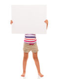 Little girl is standing on white background and holding white ca. I can hold this piece of cardboard where could be your advertisement or logo of your company Stock Photo