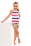 Little girl is standing on white background and holding white ca Royalty Free Stock Photo