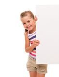 Little girl is standing on white background and holding white ca Royalty Free Stock Image