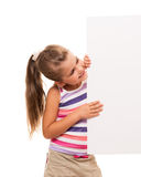 Little girl is standing on white background and holding white ca. I can hold this piece of cardboard where could be your advertisement or logo of your company Royalty Free Stock Photo