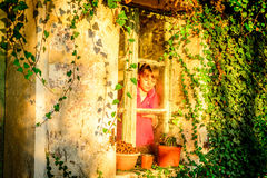 Little girl standing by the window Stock Image