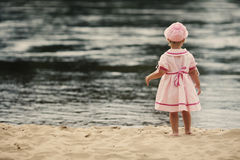 Free Little Girl Standing With Her Back On The Beach Stock Photography - 33126742