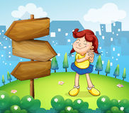 A little girl standing beside the wooden arrow boards Royalty Free Stock Images