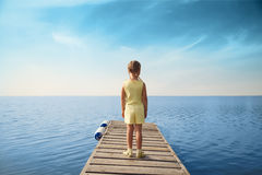 Little girl standing at wooden pier and looking to the sea. Stock Images