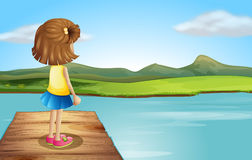 A little girl standing at the wooden port Stock Photography