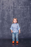 Little girl stands. Against the backdrop of concrete wall Royalty Free Stock Photography