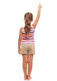 A little girl stands back, points finger somewhere up. There is something interesting just there Stock Image