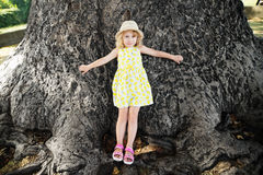 Little girl stands at the base of a large tulip tree. Royalty Free Stock Image