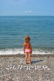 Little girl stands on beach near water. Royalty Free Stock Photography