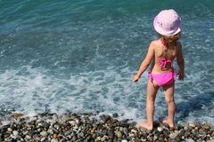 Little girl stands on beach, rear view Stock Photo