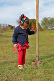 Little girl stands with big garden spade in her hand Royalty Free Stock Images