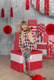 Little girl stands in a big gift box in white-red studio Royalty Free Stock Photography