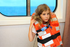 Little girl stands in cabin of ship. Sad little girl dressed in life jacket stands near window in cabin of ship Royalty Free Stock Photography