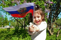 Little girl stands with flag of Russia in front of lilac Bush on sunny day Royalty Free Stock Image