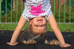 Little girl stands on her hands and smiles. stock image
