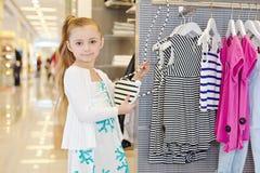 Little girl stands holding female handbag Royalty Free Stock Images