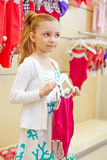 Little girl stands holding hanger with closed swimsuit. And turning something in mind Stock Photo