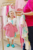 Little girl stands holding hanger with jacket and looks at mother Stock Image