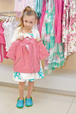 Little girl stands holding hanger with jacket Stock Image