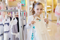 Little girl stands holding hanger with white gown Stock Photos