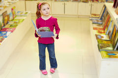 Little girl stands holding open book Stock Photo