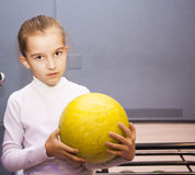 Little girl stands and holds the ball in bowling club Royalty Free Stock Photos