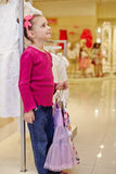 Little girl stands and holds hangers with skirt Royalty Free Stock Images