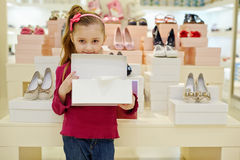 Little girl stands and holds open shoe box Stock Photos
