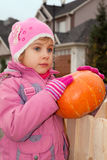 Little girl stands and holds pumpkin Royalty Free Stock Photo