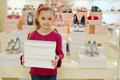 Little girl stands and holds two shoe boxes Royalty Free Stock Images