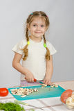 Little girl stands at kitchen table, with a smile, looking into the frame and slice the mushrooms with a knife Royalty Free Stock Photos