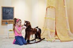 Little girl stands kneeling before hobbyhorse Stock Photos