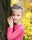 Little girl stands leaning against a tree Stock Photo