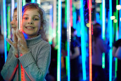 Little girl stands in mirror labyrinth. Illuminated with color lights stock images