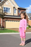 Little girl stands near cottage Royalty Free Stock Images