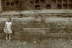 Little girl stands near the destroyed wall Stock Image