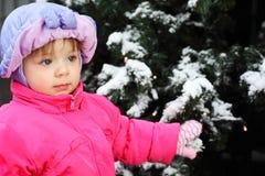 Little girl stands near green tree Stock Photos