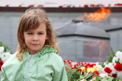 Little girl stands near memorial