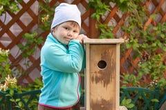 Little Girl Stands Near New Handmade Nesting Box Stock Photo