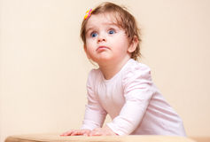 Little girl stands near the sofa at home. Royalty Free Stock Photo