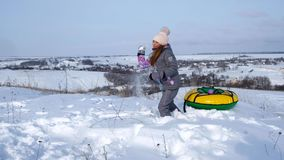 A little girl stands near the tube and plays with her sister with snow stock footage