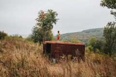 Little girl stands on the old trailer in the woods Stock Image