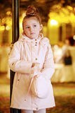 Little girl stands pensively fumbling in handbag Royalty Free Stock Photos