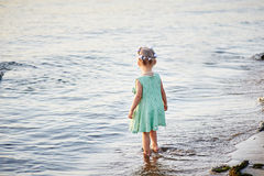 Little girl stands on the river bank Royalty Free Stock Image