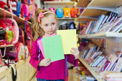 Little girl stands in school department of store Royalty Free Stock Image