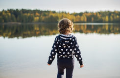 Little girl stands on shore of the Lake looks at Royalty Free Stock Photo